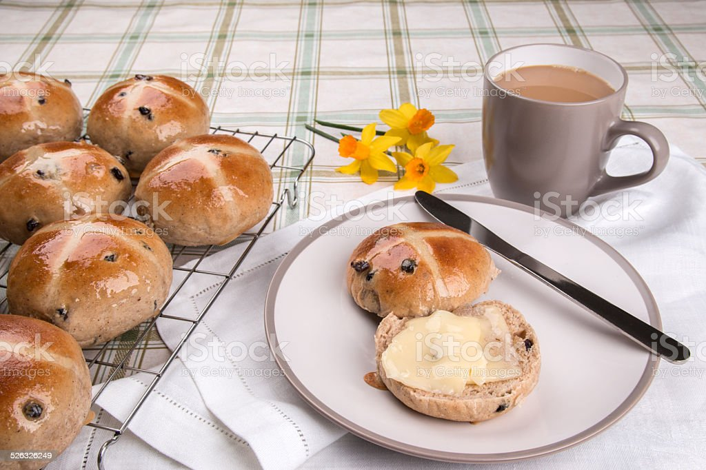 hot cross buns on cooling tray, one on plate, stock photo
