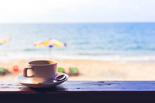 hot cup of coffee on the wood near the beach.