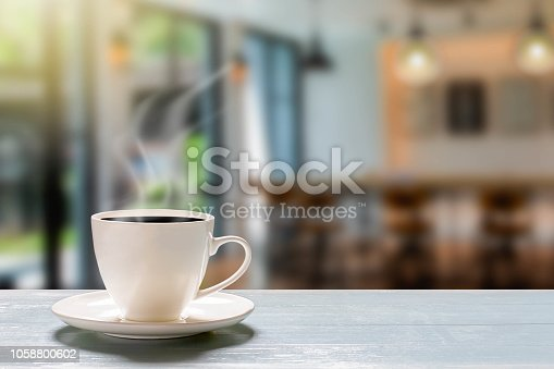 Hot cup of coffee on wooden desk on blurred coffee shop background
