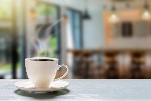 hot cup of coffee on wooden desk on blurred coffee shop background - кофейная кружка стоковые фото и изображения