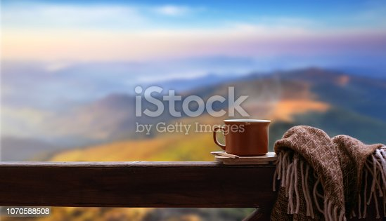 Hot cup of tea or coffee on the wooden railing on the mountains background.