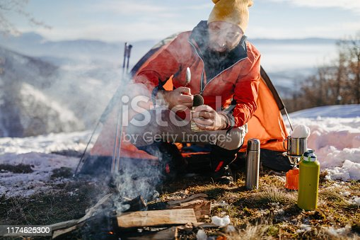 Tourist hiker eating canned food on winter hiking on snowy winter day