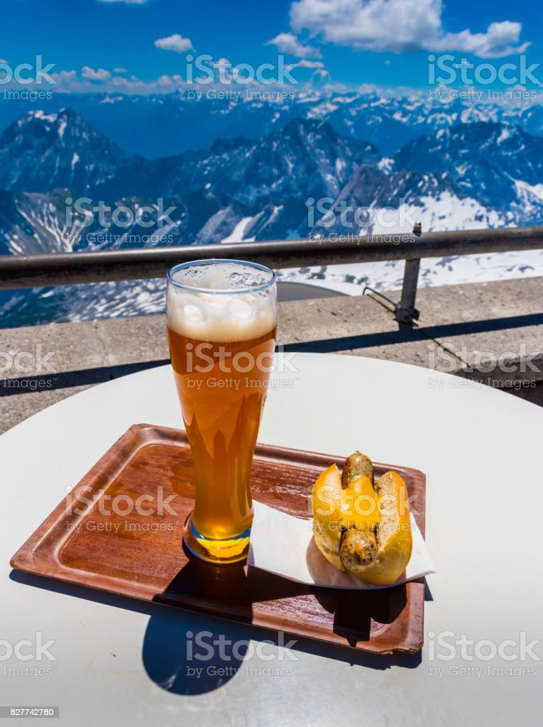 hot dog and german beer with view of alps mountain range on Zugspitze mountain , Germany stock photo