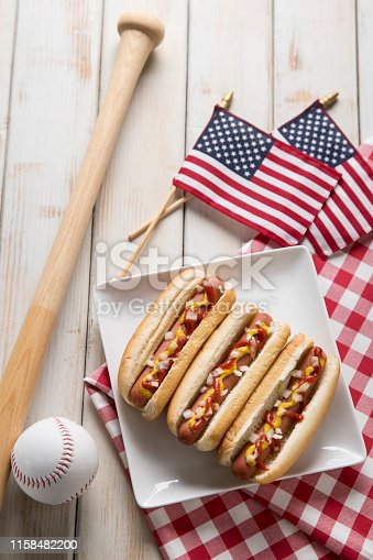 This is a photograph of three hot dogs on a white plate on a white wooden picnic bench. This is a great image for a Fourth of July picnic with a baseball and bat