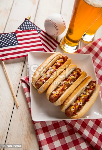 This is a photograph of three hot dogs on a white plate on a white wooden picnic bench. This is a great image for a Fourth of July picnic with beer and baseball.