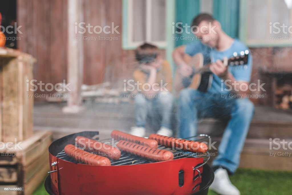 hot dog sausages on grill with family spend time together behind stock photo