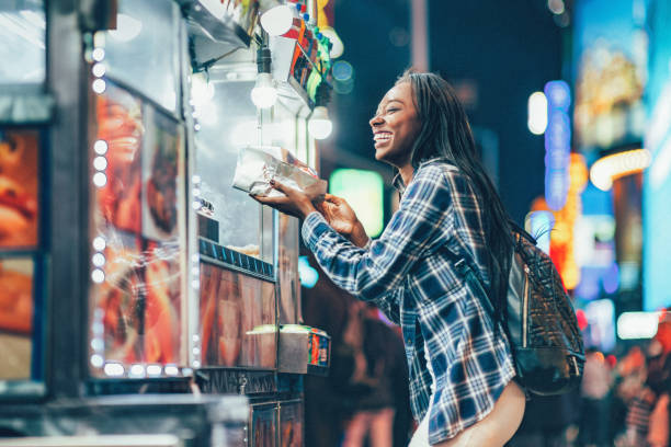 Hot Dog Stand Africa American Woman at a Hot Dog Stand in Times Square, New York City. food truck stock pictures, royalty-free photos & images