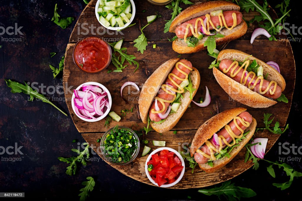 Hot dog with cucumber, tomato and red onion on wooden background. Top view. Flat lay stock photo