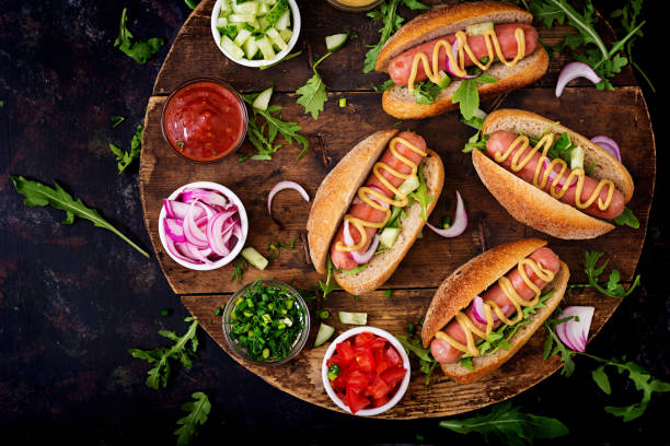 hot dog with cucumber, tomato and red onion on wooden background. top view. flat lay - hot dog stock pictures, royalty-free photos & images