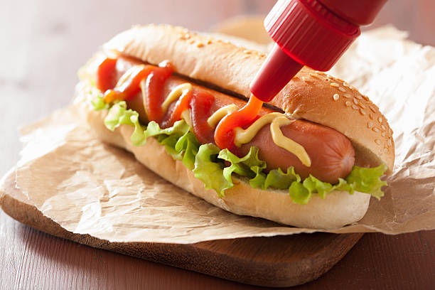 hot dog with ketchup mustard and lettuce - hot dog stock pictures, royalty-free photos & images