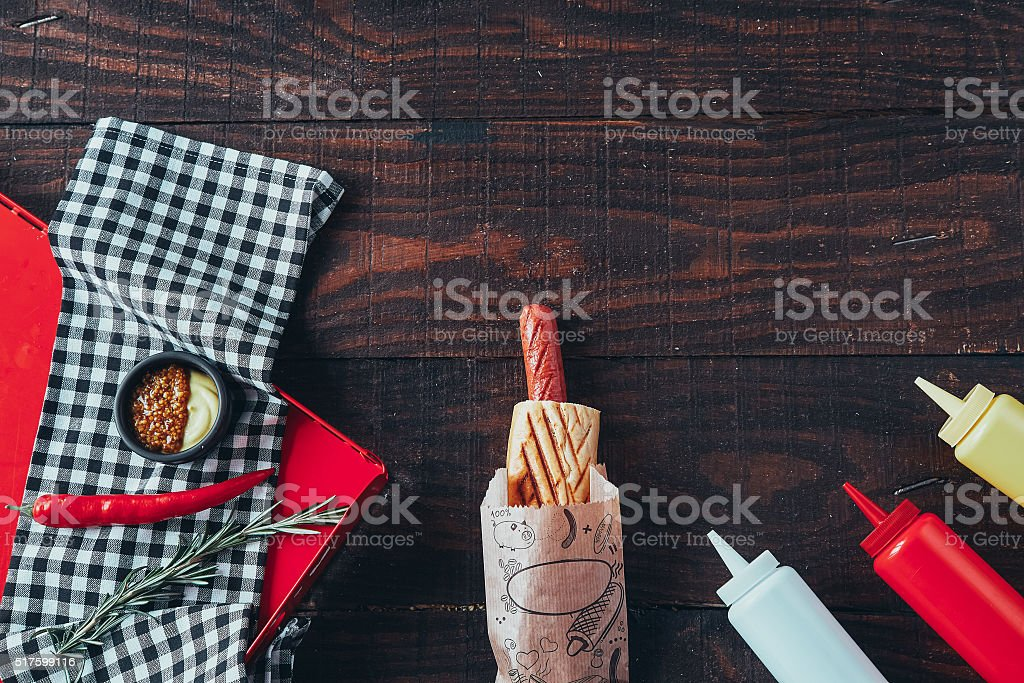 Hot dog with mustard, ketchup on wooden background. Top view stock photo
