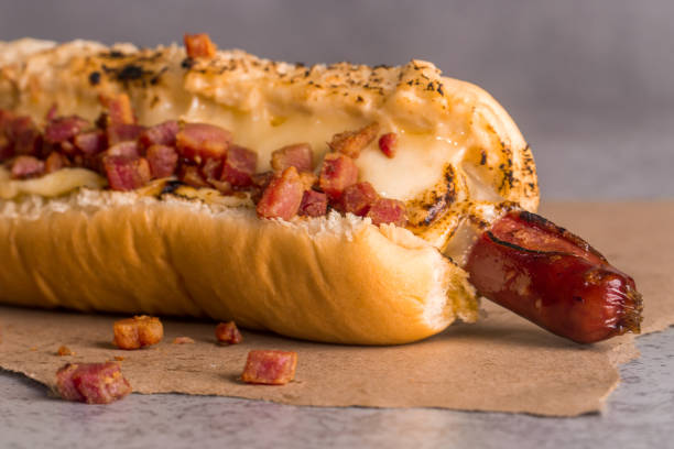 hot dog with sausage with cheese and bacon hot dog with sausage with cheese and bacon on brown paper on gray background estudio stock pictures, royalty-free photos & images