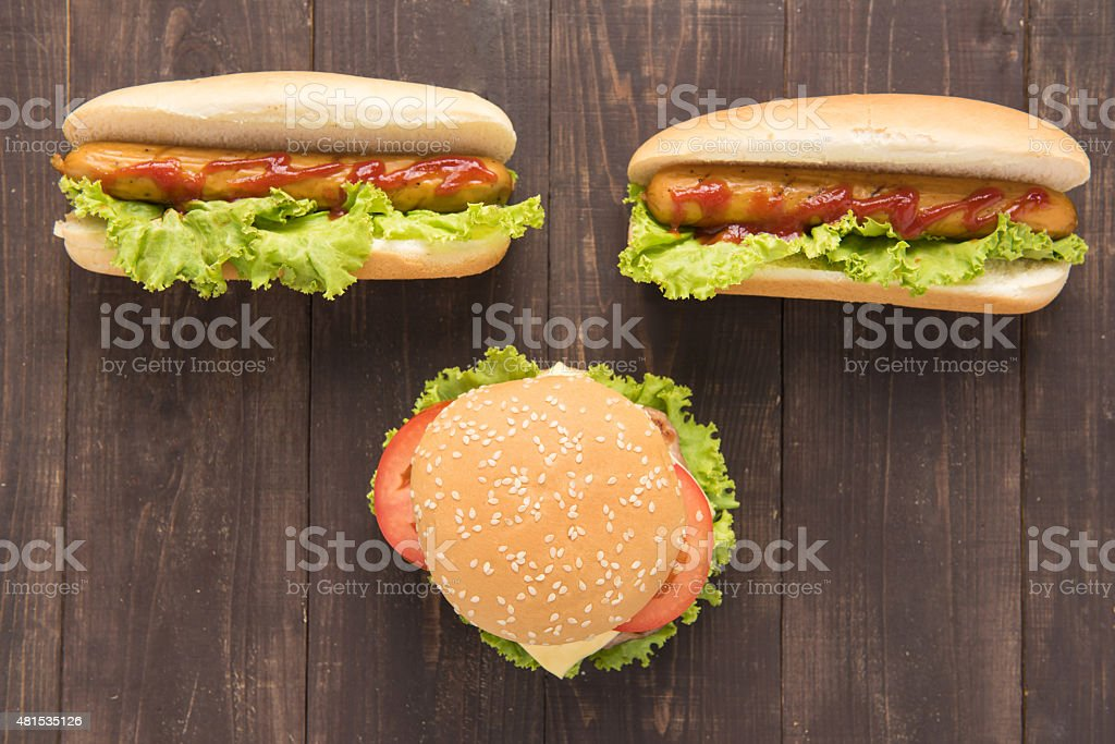 Hot dogs and hamburgers on the wooden background. stock photo