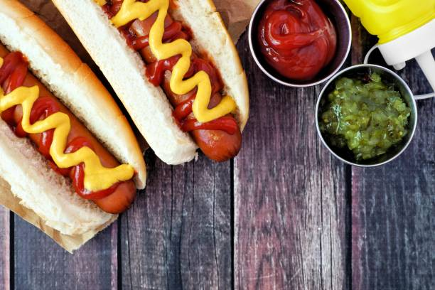 Hot dogs with mustard and ketchup, overhead scene on rustic wood stock photo