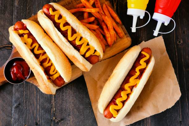 hot dogs with mustard, ketchup and fries overhead scene - hot dog stock pictures, royalty-free photos & images