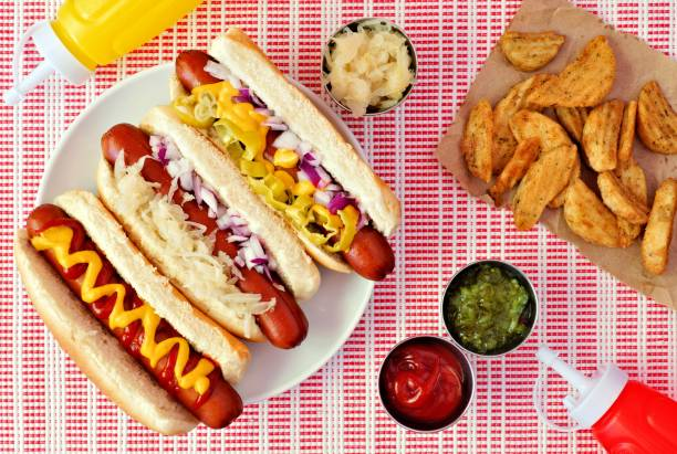Hot dogs with potato wedges, above scene on checked cloth stock photo