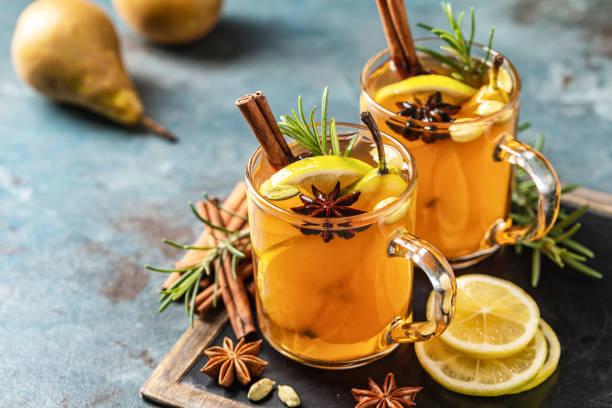 warme drank cocktail voor nieuwjaar, kerstmis, winter of herfstvakantie. toddy. glühpeer cider of gekruide thee of grog met citroen, peer, kaneel, anijs, kardemom, rozemarijn. - gluhwein stockfoto's en -beelden
