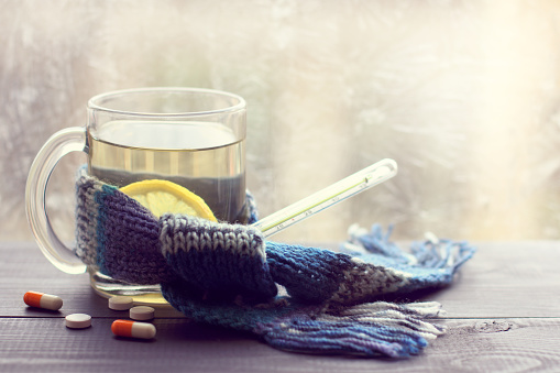 infusion lemon in the transparent mug beside thermometer and tablets on the background of a winter window