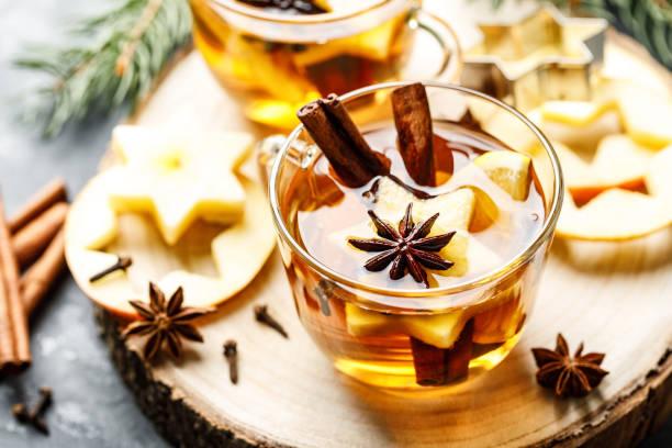 warme drank voor nieuwjaar, kerstmis of herfstvakantie. glühwein of gekruide thee of glühwein met citroen, appels, kaneel, anijs, kruidnagel. - gluhwein stockfoto's en -beelden