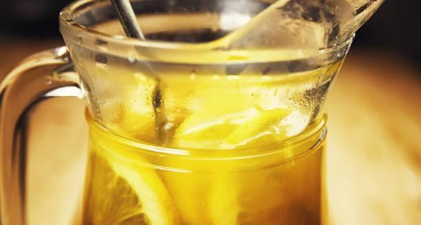 heißes getränk aus orangen-zitronen-ingwer und zimt - ingwerwasser zubereiten stock-fotos und bilder