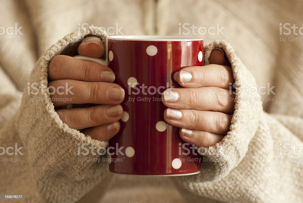 A hot drink in the hands of a young woman holding it stock photo