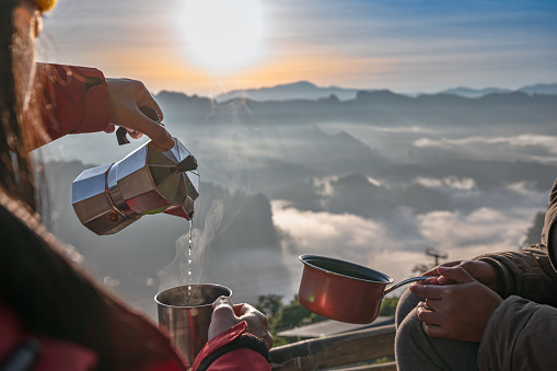 mug kettle ot water serving hot drink in the morning of mountain mist on the top peak of mountain