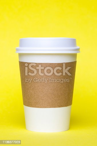 White blank disposable cup on yellow background.