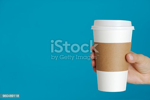 Caucasian female is holding a disposable cup in hand.
