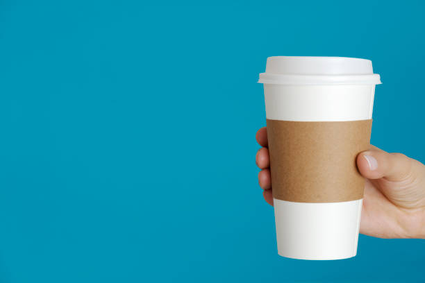 Hot Drink Caucasian female is holding a disposable cup in hand. disposable cup stock pictures, royalty-free photos & images