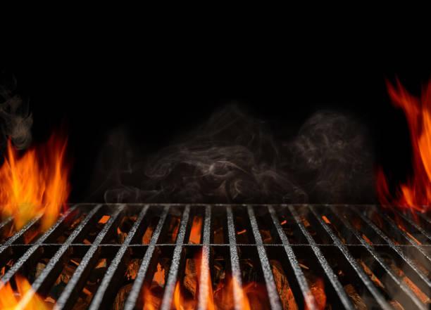 gorący pusty przenośny grill grill grill z płonącym ogniem i żarem drzewnym na czarnym tle. czekam na umieszczenie jedzenia. zbliżenie - grillowany zdjęcia i obrazy z banku zdjęć