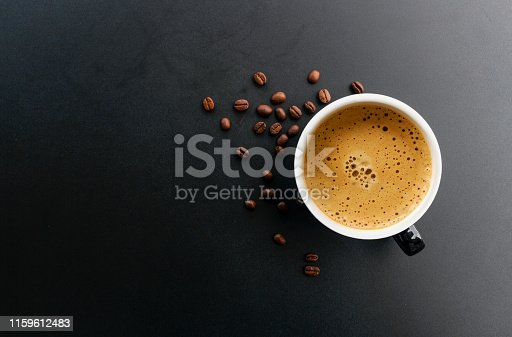 hot espresso and coffee bean on black table with soft-focus and over light in the background. top view