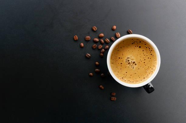 gorące espresso i ziarno kawy na czarnym stole z miękką ostrością i światłem w tle. widok z góry - coffee zdjęcia i obrazy z banku zdjęć