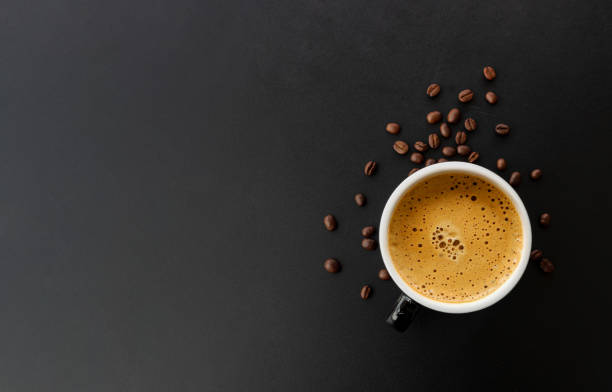 hot espresso and coffee bean on black table with soft-focus and over light in the background. top view – zdjęcie