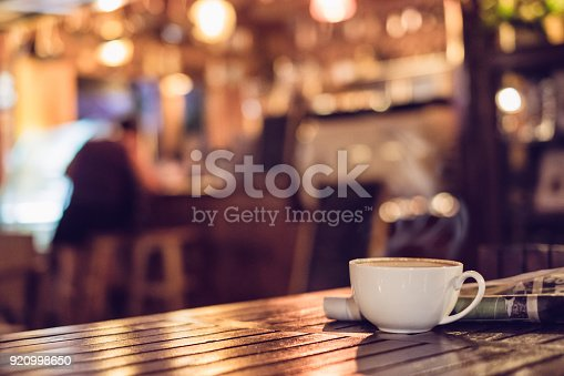 istock Hot espresso coffee cup with newspaper on wooden table lighting bokeh blur background 920998650