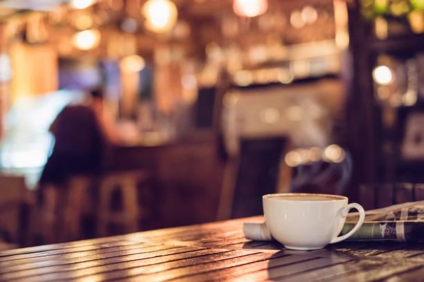 뜨거운 에스프레소 커피 컵 나무 테이블 조명 bokeh에 신문 가진 배경 흐림 - coffee 뉴스 사진 이미지
