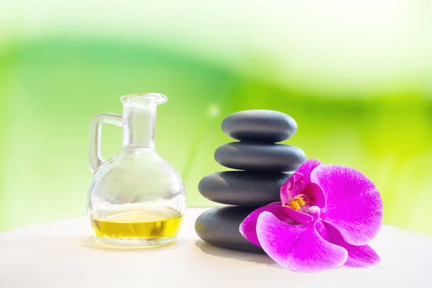 Hot fragrance oil aroma therapy massage with stone over blurred green spring garden background for relaxing image concept. stock photo