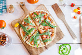 istock hot fresh homemade traditional italian pizza with cheese, tomatoes and rocked salad on wooden cooking table with ingredients. wallpaper for pizzeria and food concept. top view, flat lay 968788248
