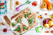 istock hot fresh homemade traditional italian pizza with cheese, tomatoes and rocked salad on wooden cooking table with ingredients. wallpaper for pizzeria and food concept. top view, flat lay 968788288