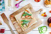 istock hot fresh homemade traditional italian pizza with cheese, tomatoes and rocked salad on wooden cooking table with ingredients. wallpaper for pizzeria and food concept. top view, flat lay 968788332