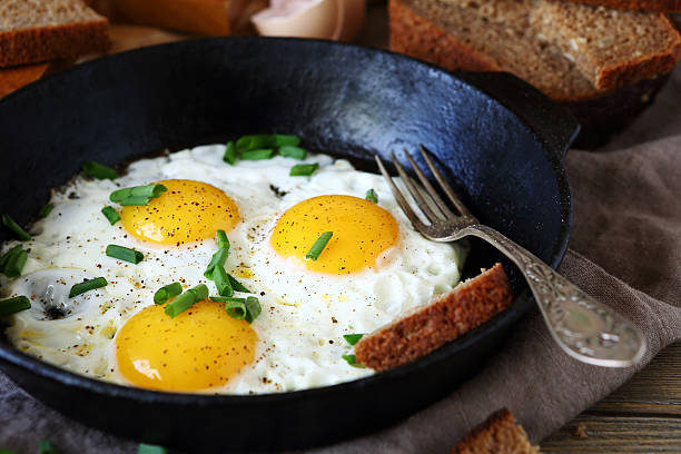 hot fried eggs in a pan - fried egg stock photos and pictures