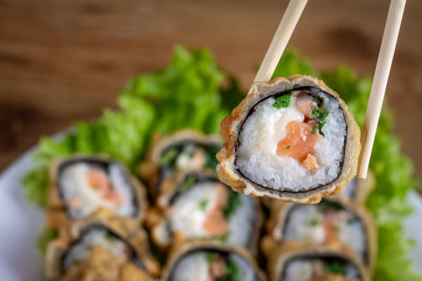 Hot fried Sushi roll with salmon, chives and cheese. Sushi menu. Japanese food. With blurred background Hot fried Sushi roll with salmon, chives and cheese. Sushi menu. Japanese food. With blurred background. estudio stock pictures, royalty-free photos & images