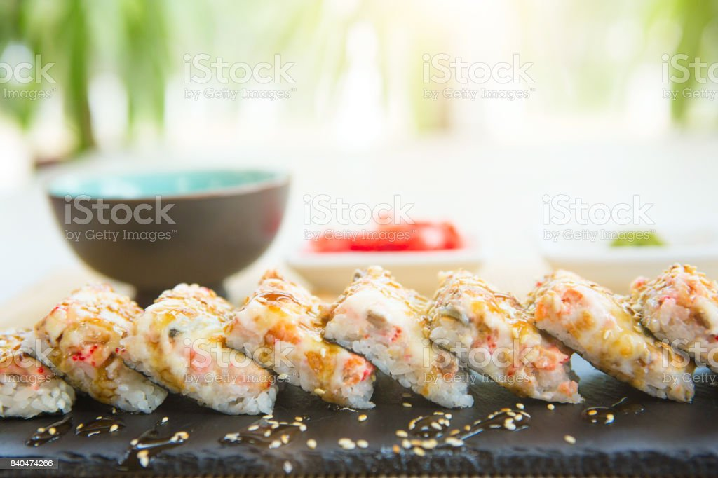 Hot fried Sushi Roll with salmon, eel, calf caviar and cheese. Sushi menu. Japanese food stock photo