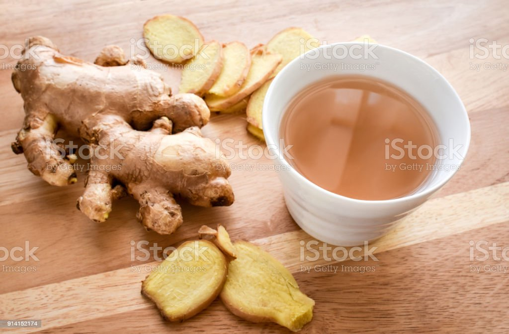 Hot ginger tea cup with ginger roots on wood background. stock photo
