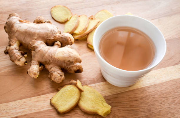 hot ginger tea cup with ginger roots on wood background. - ginger stock photos and pictures