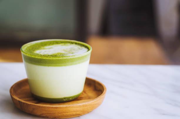 heißer grüner tee spät mit modernem stil und köstlich im hölzernen platte marmortisch. - grüner tee koffein stock-fotos und bilder
