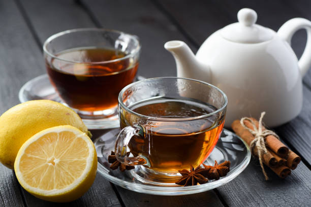 Hot healthy beverage. Black tea with lemon and spices on black background stock photo