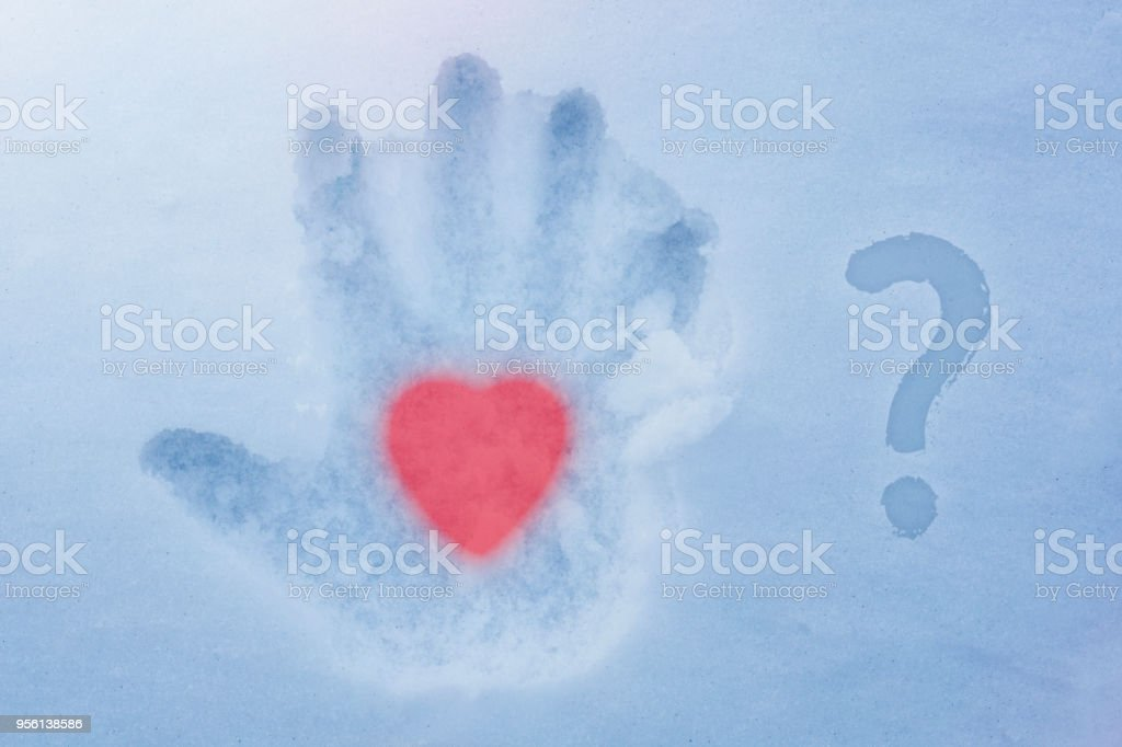 A hot heart in a cold hand and a question mark stock photo