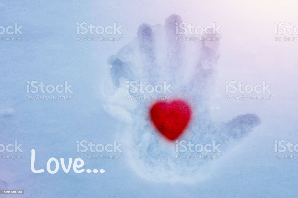 Hot heart in a cold hand and the word LOVE stock photo