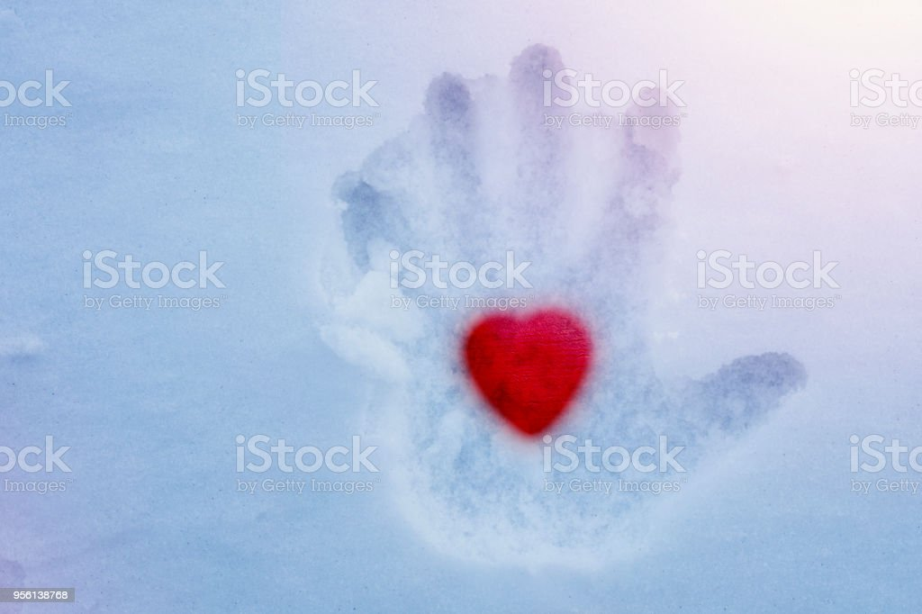 Hot heart in a cold hand stock photo