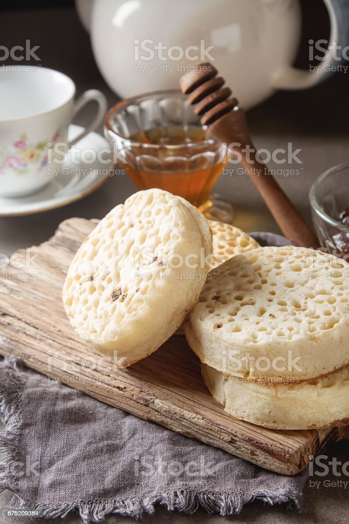 Hot Home made toasted crumpets served with honey and jams. Dark wood background. British breakfast. royalty-free stock photo